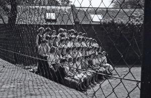 Photograph of female students gathered by a tennis court for a photograph behind Masson Hall (George Square), University of Edinburgh <br /><br />