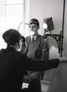 Photograph of a man shining a light in Hugh Cuthbert&#039;s mouth<br /><br />